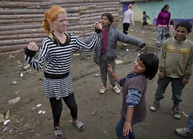 Minka Ruseva, daughter of Sasha Ruseva, left, dances along with other children in a Roma neighborhood of Nikolaevo, Bulgaria, Friday, Oct. 25, 2013. Sasha Ruseva, a Bulgarian Roma woman from this  ...