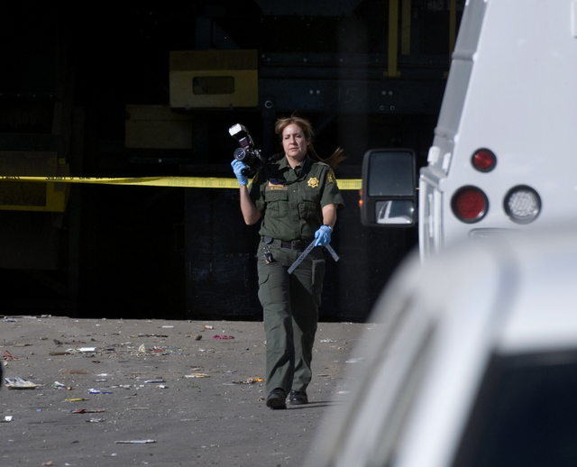 A San Bernardino County Sheriff's Scientific Investigations service specialist walks out of the Materials Recycling Facility in Victorville, Calif., on Thursday, Oct. 24, 2013. Authorities say a w ...