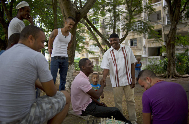 U.S. citizen William Potts, second from right, greets his neighbors playing chess near his home in Havana, Cuba, Friday, Oct. 25, 2013. Years after he hijacked a plane traveling from Newark to Mia ...