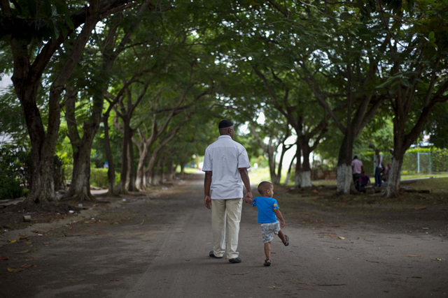 U.S. citizen William Potts walks with his nephew Daniel Rodriguez along a street in his neighborhood in Havana, Cuba, Friday, Oct. 25, 2013.  Years after he hijacked a plane traveling from Newark  ...