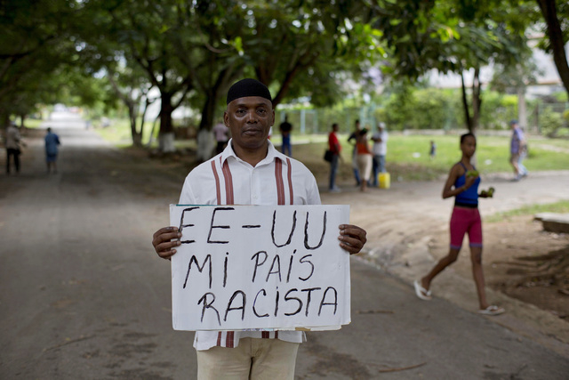 """U.S. citizen William Potts poses with a sign that reads in Spanish """"USA my racist country"""" in Havana, Cuba, Friday, Oct. 25, 2013. Years after he hijacked a plane traveling from Newark t ..."""