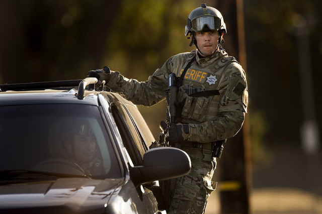 Police converge on a house where Sammy Duran is suspected to be residing on Friday, Oct. 25, 2013, in Roseville, Calif. Duran is a suspect in the shooting of three law enforcement officers that oc ...