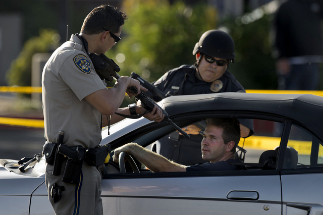 A California Highway Patrol officer and another emergency responder stop a vehicle at a checkpoint near the neighborhood where a federal immigration officer was shot and three local police officer ...