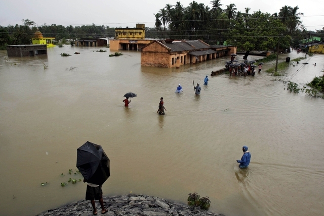 Villagers wade through floodwaters in Banapur village, in Khurda district, in the eastern Indian state of Orissa, Friday, Oct. 25, 2013. Low pressure induced rains has flooded several parts of the ...