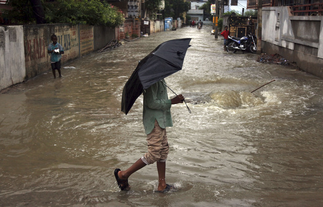 An Indian man holds an umbrella and crosses a flooded street in Hyderabad, India, Friday, Oct. 25, 2013. Heavy rains triggered by northeast monsoon have lashed several parts of Andhra Pradesh stat ...