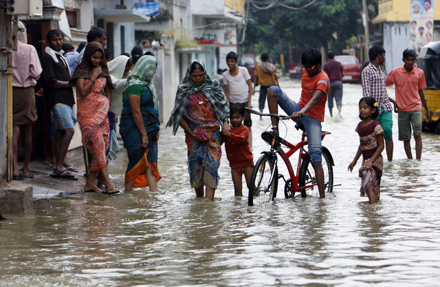 Indians wade through a flooded street in Hyderabad, India, Friday, Oct. 25, 2013. Heavy rains triggered by northeast monsoon have lashed several parts of Andhra Pradesh state for the fourth consec ...
