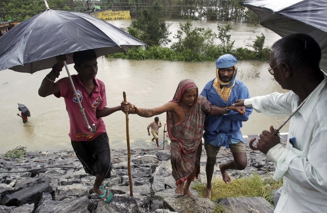 Indian villagers help an elderly woman to safer ground after crossing floodwaters in Khurda district, in the eastern Indian state of Orissa, Friday, Oct. 25, 2013. Low pressure induced rains has f ...