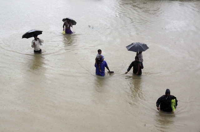 Villagers wade through floodwaters to reach safer areas in Khurda district, in the eastern Indian state of Orissa, Friday, Oct. 25, 2013. Low pressure induced rains has flooded several parts of th ...