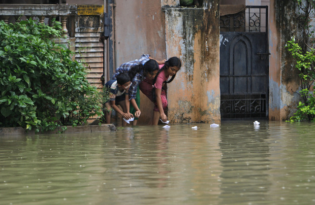 Indian children play with paper boats outside their flooded home in Hyderabad, India, Friday, Oct. 25, 2013. Heavy rains triggered by northeast monsoon have lashed several parts of Andhra Pradesh  ...
