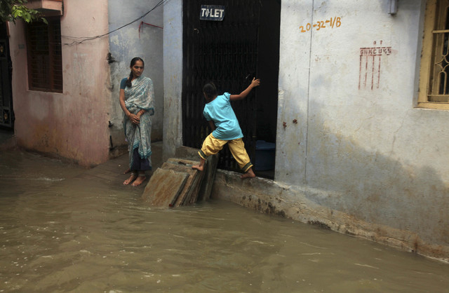 An Indian child balances herself on dry area as she crosses a flooded street in Hyderabad, India, Friday, Oct. 25, 2013. Heavy rains triggered by northeast monsoon have lashed several parts of And ...