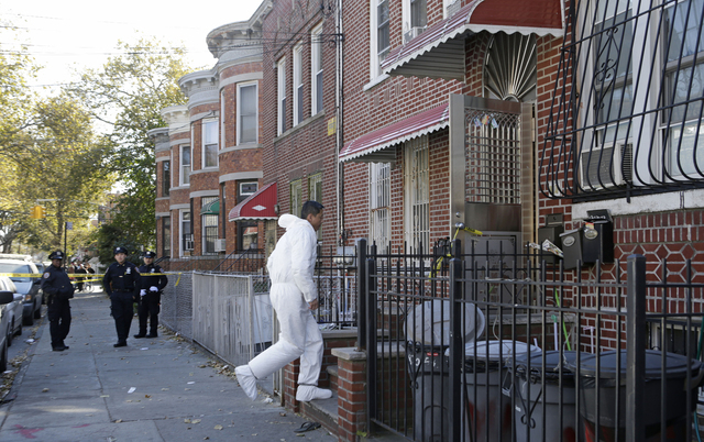 A crime scene detective leaps up the steps at the scene of a multiple fatal stabbing Sunday, Oct. 27, 2013, in the Sunset Park neighborhood of Brooklyn, in New York. Police said a mother and her f ...