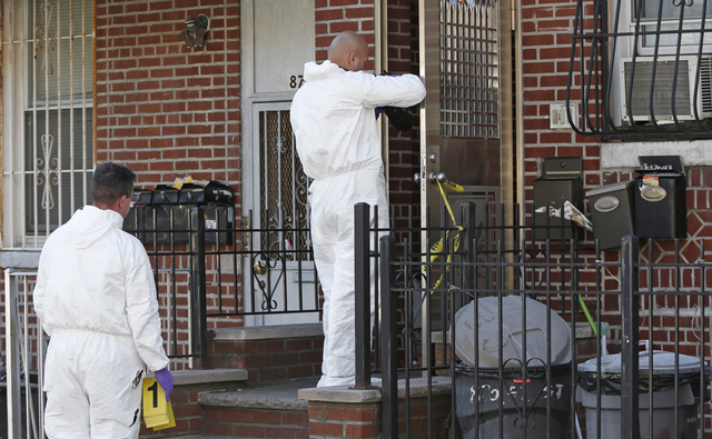 Crime scene detectives investigate the scene of a multiple fatal stabbing Sunday, Oct. 27, 2013, in New York. Police said a mother and her four young children were stabbed to death in a brutal ram ...