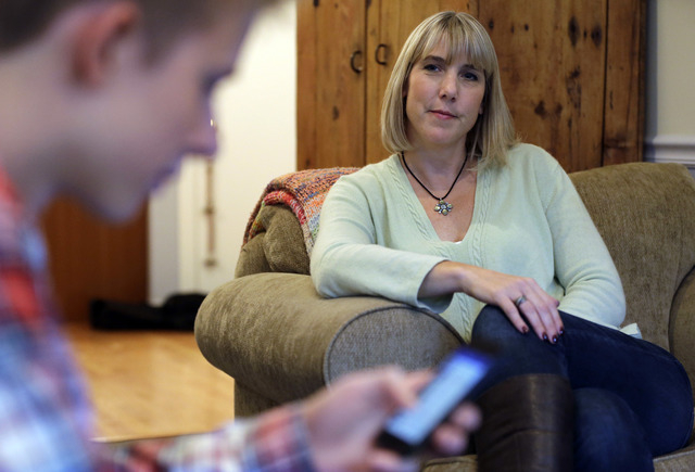 In this Oct. 24, 2013 photo, Amy Risinger, right, watches her son Mark Risinger, 16, at their home in Glenview, Ill. Mark Risinger is allowed to use his smartphone and laptop in his room, and says ...