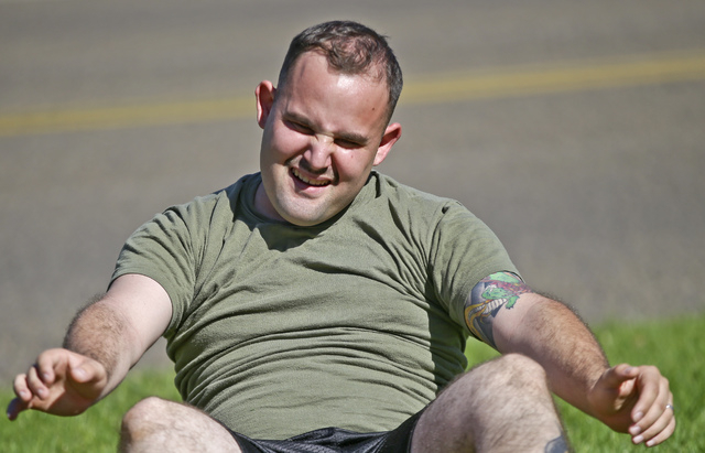 """In a Wednesday, Oct. 16, 2013 photo,  overweight service member who failed the so-called """"tape test"""" struggles doing sit ups during a workout where he hopes to improve his conditioning a ..."""