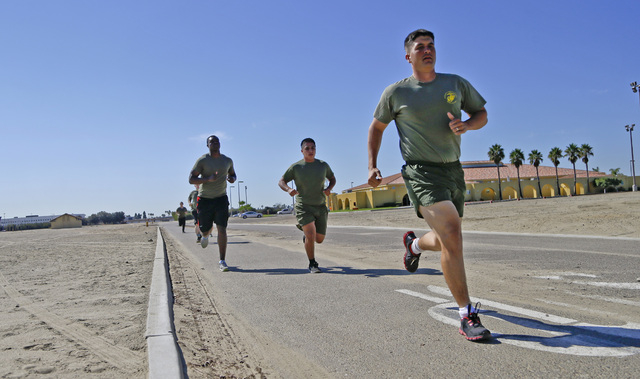 In a Thursday, Oct. 17, 2013 photo, an instructor pulls away from a group of service members on a three mile run at the Marine Corps Recruit Depot in San Diego.  The group members have failed the  ...
