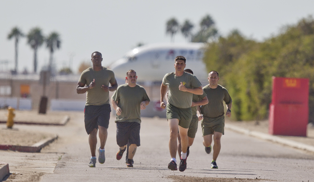 """In a Thursday, Oct. 17, 2013 photo, a group of sailors and Marines who failed the so-called """"tape test'' are led by an instructor on a three mile run as they work to improve their fitness and ..."""