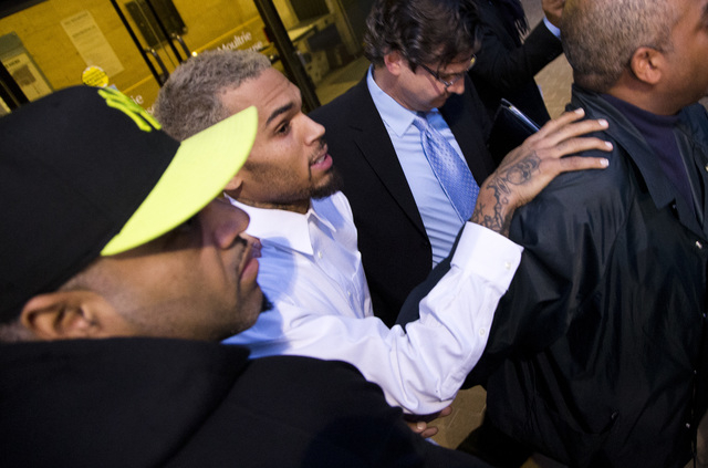 Singer Chris Brown is surrounded by bodyguards as he departs the H. Carl Moultriel courthouse Monday, Oct. 28, 2013, with one of his attorney's, Danny Onorato, second from right, in Washington. A  ...