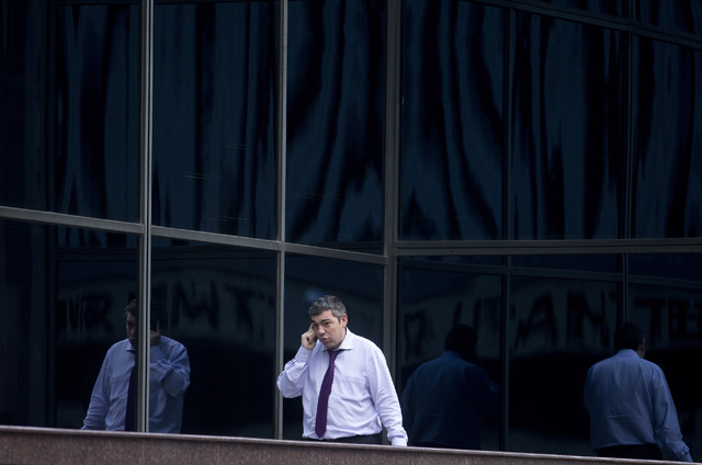 In this Thursday, Jan. 17, 2013, file photo, a man speaks on a cell phone in the business district of Madrid. A Spanish newspaper published a document Monday, Oct. 28, 2013, that it said shows the ...