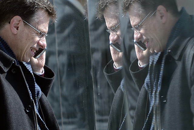 In this Tuesday, Feb. 26, 2013, file photo, a man is reflected in paneling as he speaks on his phone at the Mobile World Congress, the world's largest mobile phone trade show, in Barcelona, Spain. ...