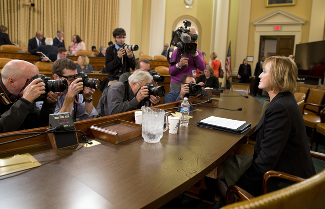 Photographers surround Marilyn Tavenner, the administrator of the Centers for Medicare and Medicaid Services as she prepares to testify Tuesday on Capitol Hill in Washington before the House Ways  ...