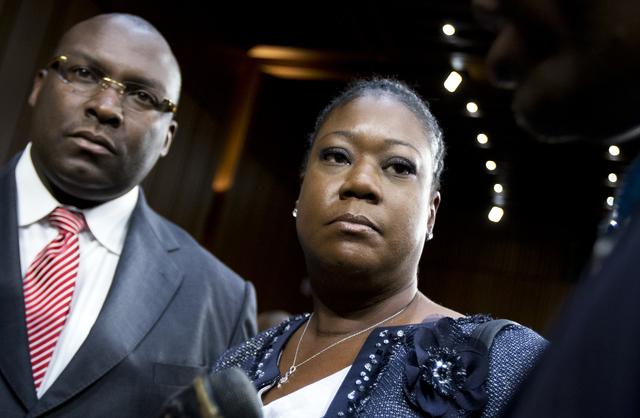 Sybrina Fulton, mother of Trayvon Martin, center, and her lawyer Daryl Parks, right, stand in the hearing room at the conclusion of a Senate Judiciary Subcommittee on the Constitution, Civil Right ...
