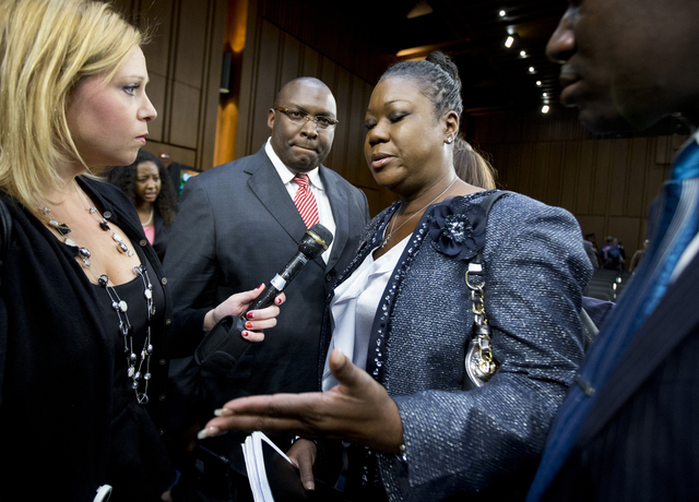 Sybrina Fulton, mother of Trayvon Martin, center, stands next to her lawyers Daryl Parks, second from left, and Benjamin Crump as she speaks to a reporter at the conclusion of a Senate Judiciary S ...