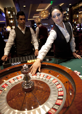 Ioana Hornyak, right, and Hamid Osmani, roulette dealers at The Cosmopolitan of Las Vegas, work the roulette table on April 18. Casino companies have lowered their estimates to pre-recession rates ...