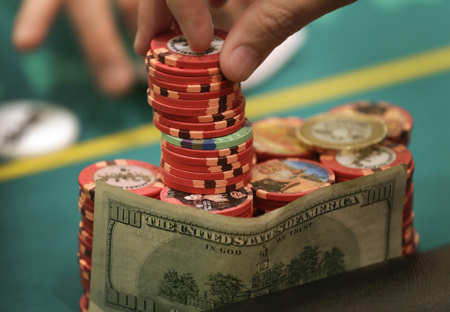 A poker player takes his ante from his stack of chips during a game of Texas Hold 'em on Feb. 27 in Las Vegas. (AP Photo/Julie Jacobson, File)