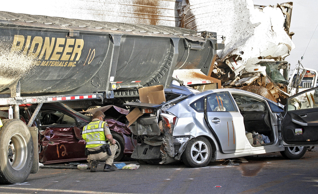 CORRECTS SPELLING OF CITY TO CASA GRANDE INSTEAD OF CASE GRANDE - Arizona Department of Public Safety officers investigate a multiple fatality accident involving six semi tractor-trailers and 19 o ...