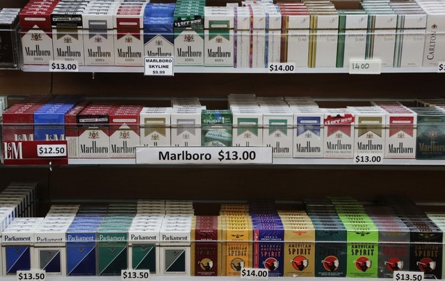 In this March 18, 2013 file photo, cigarette packs are displayed at a convenience store in New York. On Wednesday, Oct. 30, 2013, law makers in New York City voted to raise the cigarette-buying ag ...