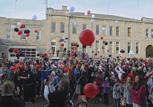 In this Oct. 28, 2013 photo, balloons are released as a large crowd sings Christmas carols outside of Devin Kohlman's home in Port Clinton, Ohio. Kohlman, who has been battling an aggressive form  ...