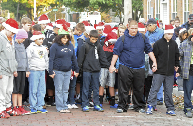 In this Oct. 28, 2013 photo, members of the Port CLinton, Ohio community pause for a moment of silence during a ceremony for Devin Kohlman outside his home. Kohlman, who has been battling an aggre ...