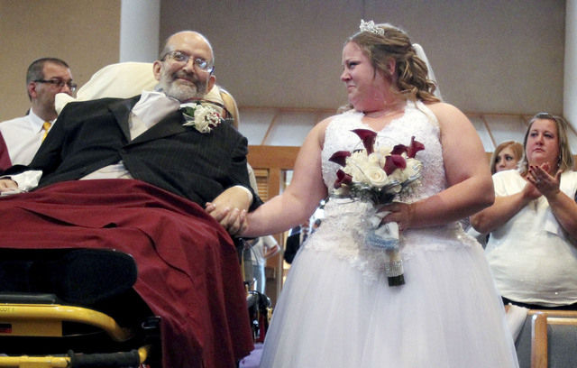 FILE - In this Oct. 12, 2013 file photo, bride Sarah Nagy, right, begins to cry as she is escorted by her father, Scott, down the aisle during her wedding ceremony in Strongsville, Ohio. Scott Nag ...