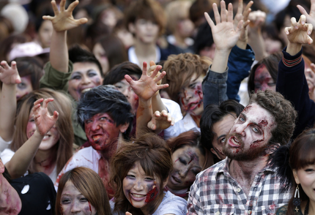 Participants in zombie costumes, perform during a Halloween event at Tokyo Tower in Tokyo, Thursday, Oct. 31, 2013. (AP Photo/Shizuo Kambayashi)
