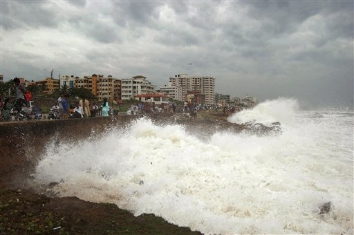Indian people watch high tide waves as they stand at the Bay of Bengal coast in Vishakhapatnam, India, Saturday, Oct. 12, 2013. Hundreds of thousands of people living along India's eastern coastli ...