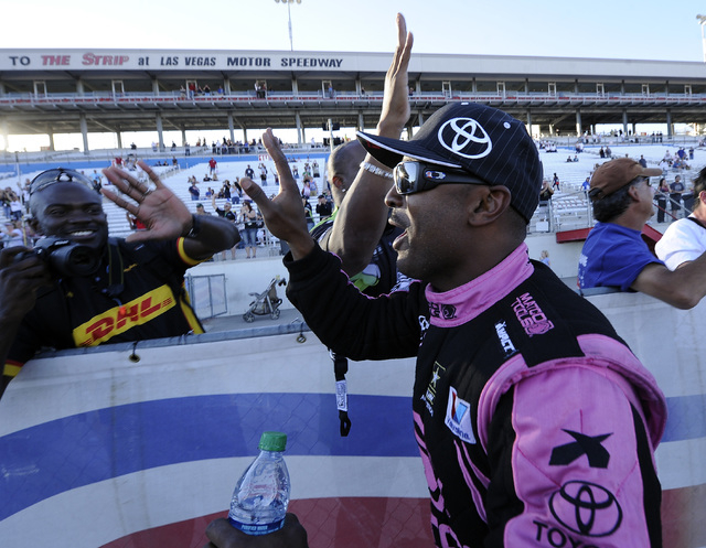 NHRA top Fuel driver Antron Brown high fives fans after winning the NHRA Top Fuel finals Sunday at the Las Vegas Motor Speedway. (Josh Holmberg/Las Vegas Review-Journal)