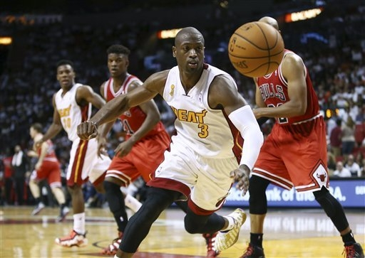 Miami Heat's Dwyane Wade chase a ball during the second half of a NBA basketball game in Miami, Tuesday, Oct. 29, 2013 against the Chicago Bulls. The Heat won 107-95. (AP Photo/J Pat Carter)