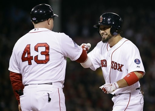 Boston Red Sox's Shane Victorino is congratulated by first base coach Arnie Beyeler after hitting an RBI single during the fourth inning of Game 6 of baseball's World Series against the St. Louis  ...