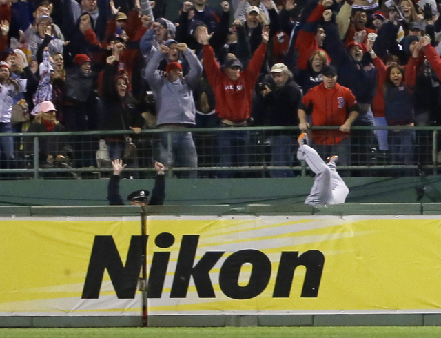 Boston Police officer Steve Horgan celebrates as Detroit Tigers' Torii Hunter falls over the right field fence into the bullpen trying to catch a grand slam hit by Boston Red Sox' David Ortiz duri ...