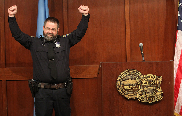 Boston Police Officer Steve Horgan, raises his hands as he poses for a photograph during a news conference on Tuesday, Oct. 15, 2013 in Boston. Horgan says he's humbled by the attention he's recei ...