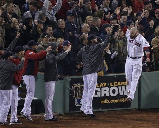 Boston Red Sox's Jonny Gomes celebrates with teammates after scoring during the third inning of Game 6 of baseball's World Series against the St. Louis Cardinals Wednesday, Oct. 30, 2013, in Bosto ...