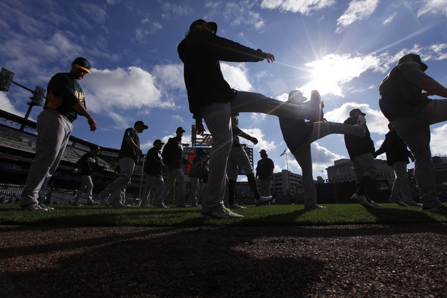 The Oakland Athletics stretch before batting practice for Game 3 of an American League baseball division series against the Detroit Tigers in Detroit on Monday. (AP Photo/Paul Sancya)