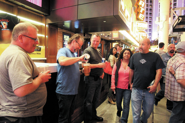 Friends, from left, Tom McCarthy, Glenn Kean and Bill Finn, all of Canada, drink beer at the Fremont Street Experience Friday, Oct. 4, 2013. More than 1,300 open container violations have been tos ...