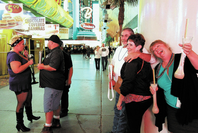 """Revelers, from left, Seana Brown, a man who gave his name as """"Tatonka,"""" Mike Canter, Virginia Graves and Wendy Mitchell drink at the Fremont Street Experience Friday, Oct. 4, 2013. More  ..."""