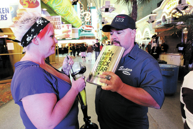 """Seana Brown, left, and a man who gave his name as """"Tatonka,"""" drink at the Fremont Street Experience Friday, Oct. 4, 2013. More than 1,300 open container violations have been tossed from  ..."""