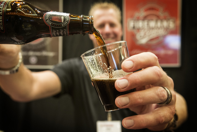 Robert Nowaczyk, founder and chairman of Fireman's Brew,  pours German Doublebock style beer at the brewery's booth during the National Beer Wholesalers Association Convention and Trade show at Ca ...