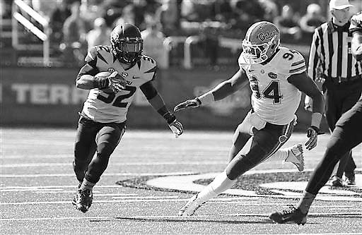 Missouri running back Russell Hansbrough runs with the ball as Florida Gators defensive lineman Bryan Cox Jr. defends during the second quarter of an NCAA college football game Saturday, Oct. 19,  ...