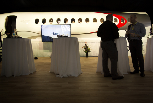 Men stand beside the fuselage of the Dassault Falcon X5 aircraft inside the company's corporate tent at  the National Business Aviation Association Static Display of Aircraft on Tuesday, Oct. 22,  ...