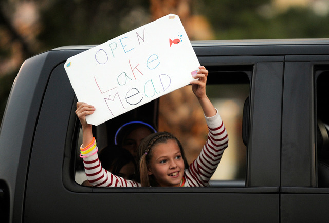 Young protester Adison Milne holds a sign to open Lake Mead as she rides in a truck hauling a boat up the Las Vegas Strip protesting the closure of the Lake Mead National Recreation Area on Sunday ...