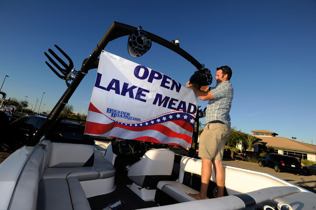 Dan Lee ties a banner on his boat before he and several dozen other boaters proceed up the Las Vegas Strip protesting the closure of the Lake Mead National Recreation Area on Sunday, Oct. 6, 2013. ...